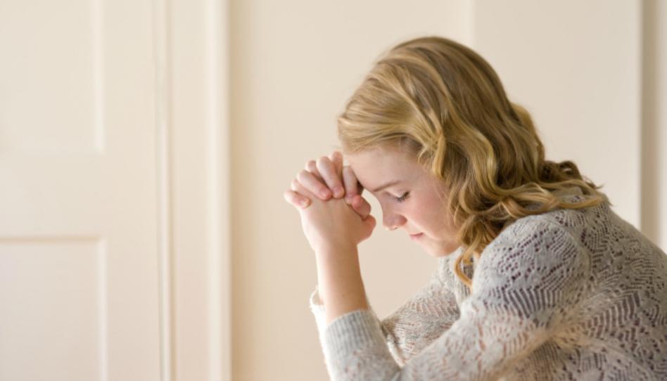 Mladá žena, která se modlí