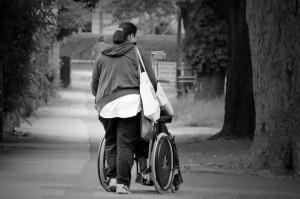 Paní, která vede postižehnou ženu na vozíku