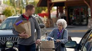 Muž, který pomáhá staré ženě s nákupem