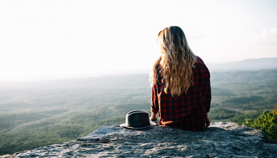 divka sedi na hrane skaly lide jsou aby meli radost, ale co kdyz se tak necitime