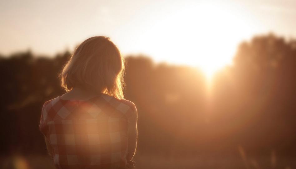Zena stoji a diva se na zapad slunce