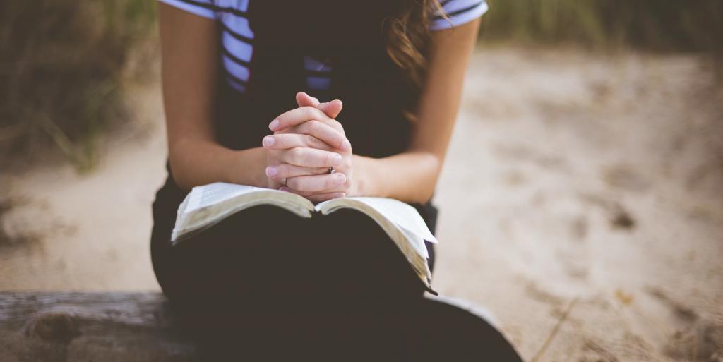 Žena s biblí se modlí